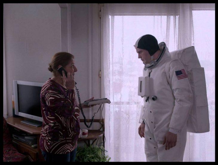 una señora con un teléfono en la oreja al lado de un joven vestido de astronauta