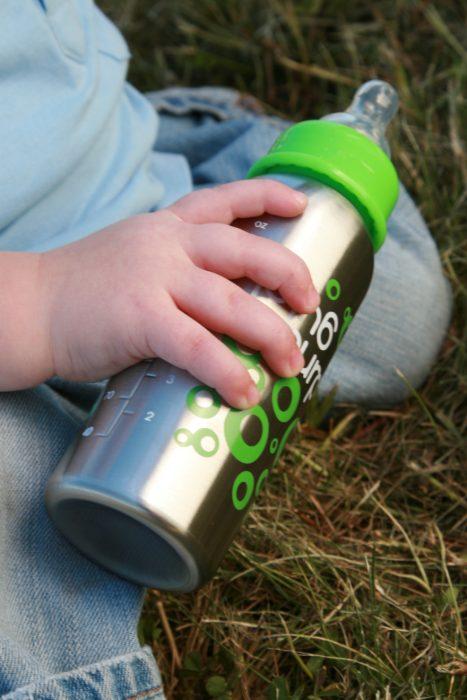 bebé sosteniendo un biberón ecológico