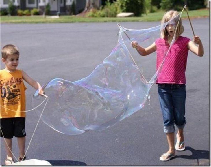 niños jugando con burbujas gigantes