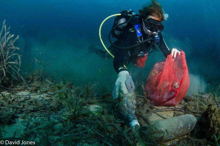 buzo en un océano lleno de plástico