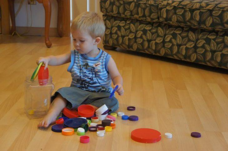 niño jugando con tapas de colores