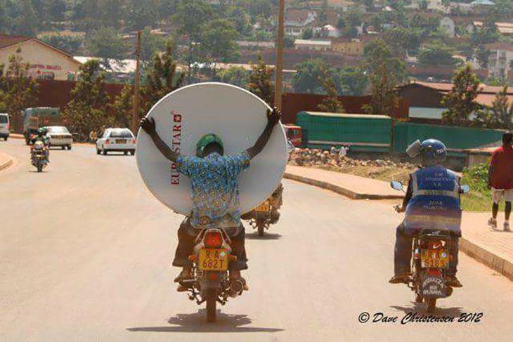 chico en moto con una antena televisiva