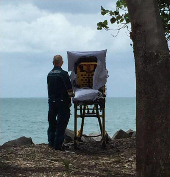 parmédico con camilla a la orilla del mar