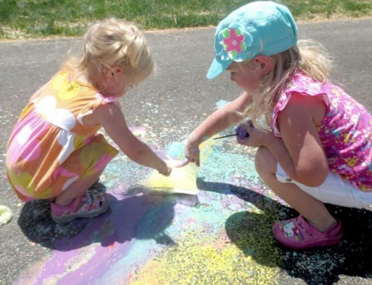 niñas explotando bolsas de pintura en el patio