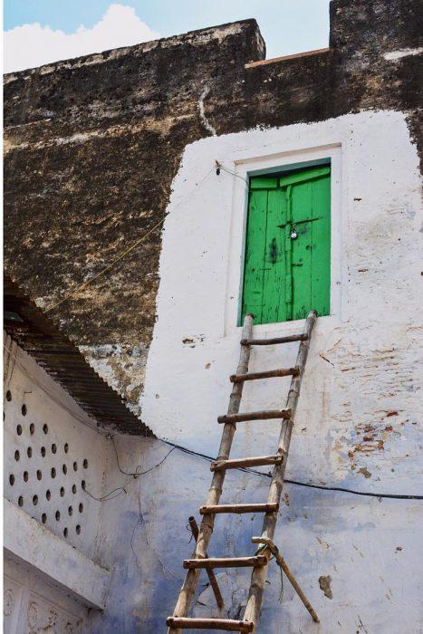 Puerta verde en el segundo piso con una escalera para subir a ella