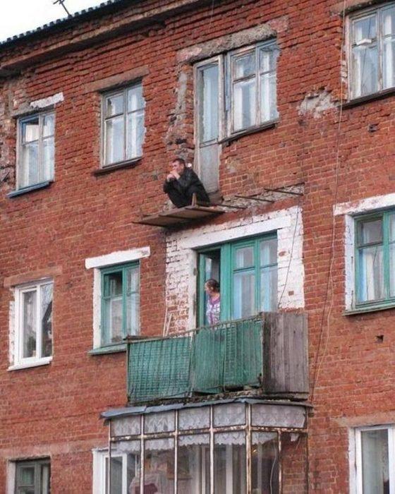 hombre en cuclillas en un balcón sin rejas