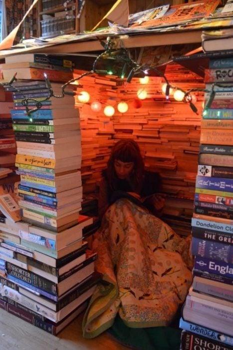chica dentro de un fuerte hecho de libros