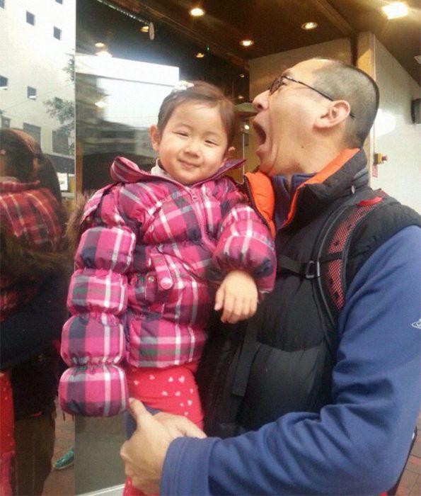 papá asiático cargando a su niña