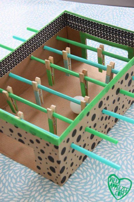 futbolito hecho de caja, pinzas para ropa y popotes