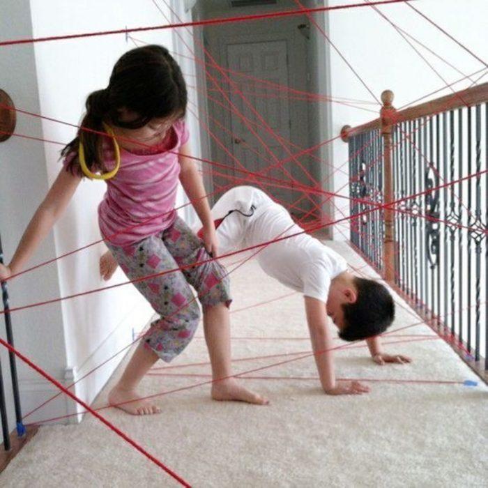 niños jugando en trampa láser de estambre