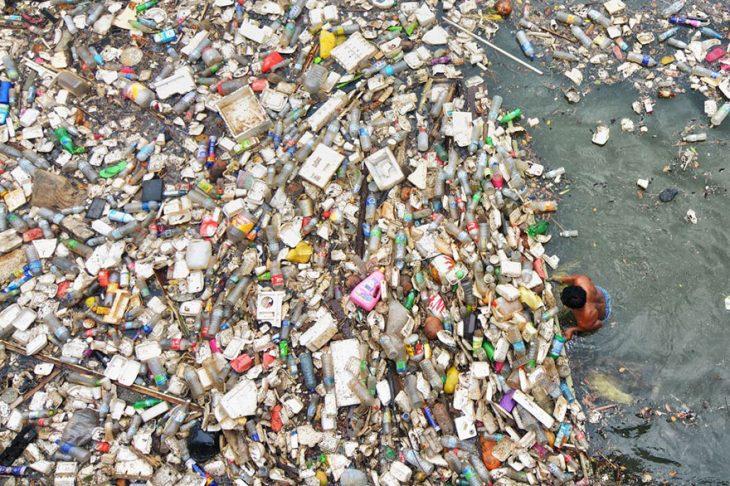 hombre en el océano con miles de botellas de plástico