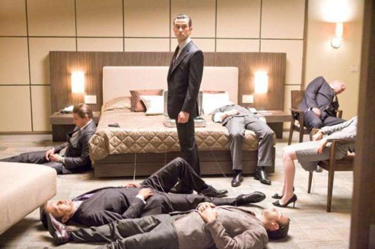 Hombre de traje negro de pie en un habitación con otros hombres de traje recostados en el suelo