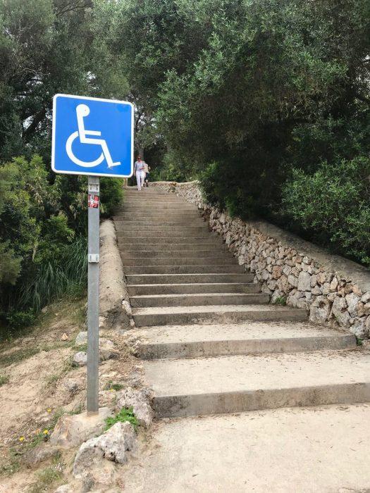 señal de discapacitados frente a unas escaleras