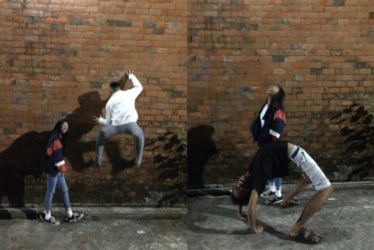 chicos posando frente a una pared de ladrillos