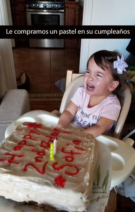 niña llorando frente a un pastel de cumpleaños