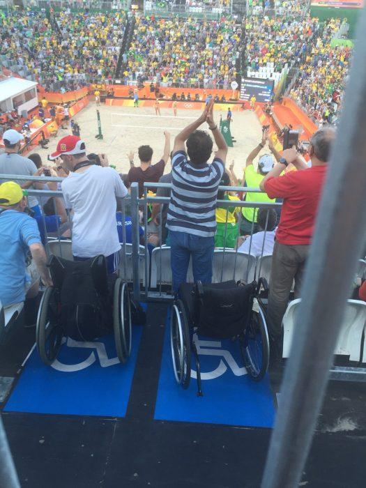 hombres de pie frente a sillas de ruedas en un partido deportivo