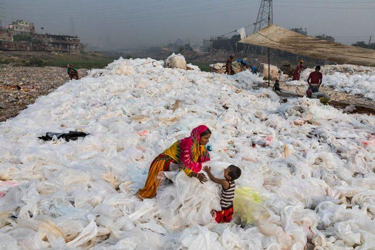 mujer con niño en medio de un basurero de plástico