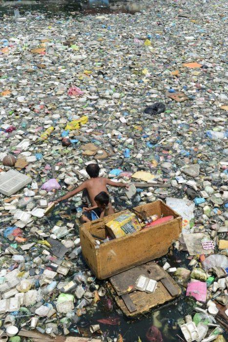 niños en un lago lleno de botellas
