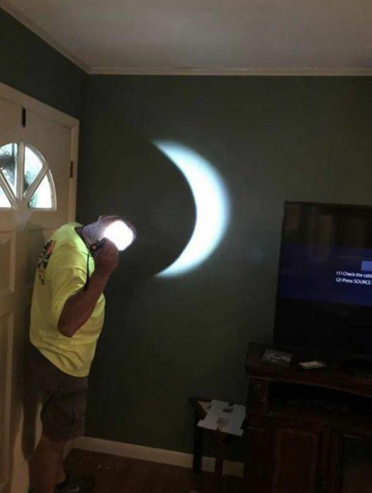 señor pryecta un eclipse en la pared con una linterna y su calva
