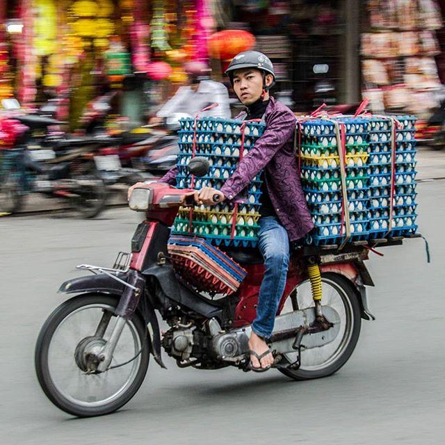 muchacho en moto cargando varias carteras de huevos