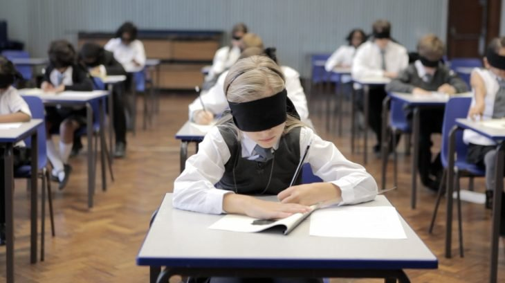 niños de primaria sentados en pupitres con vendas en los ojos, haciendo un examen