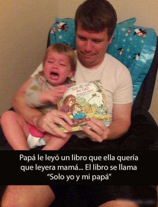 niña llorando en el regazo de su papá que le esta leyendo un libro