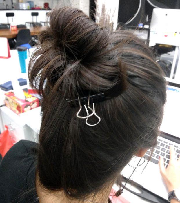 mujer se ata el pelo con un clip de oficina