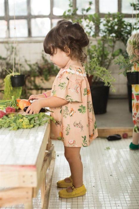 niña con un vestidito en un set con plantas