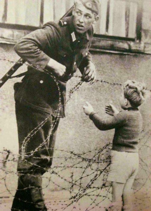 Soldado alemán ayuda a un niño a cruzar el Muro de Berlín, 1961