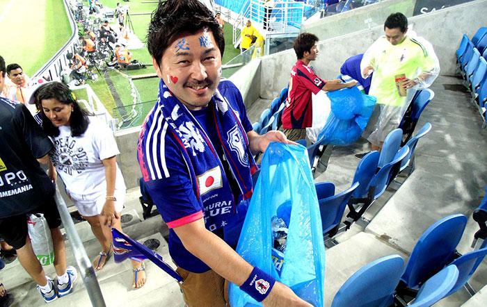 Aficionados japoneses y senegaleses recogen basura