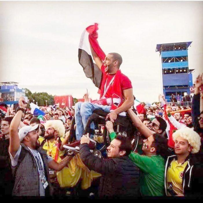 Colombianos y mexicanos cargan a un egipcio en silla de ruedas para que vea jugar a Egipto