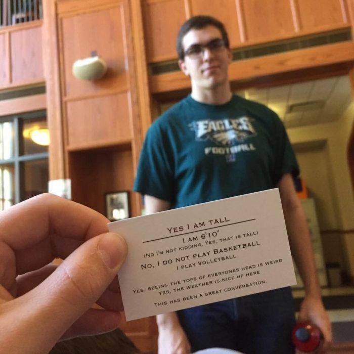 mano sosteniendo una tarjeta y detrás un chico alto
