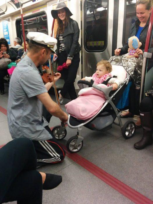 hombre toca el violín para calmar a una niña que lloraba en el metro