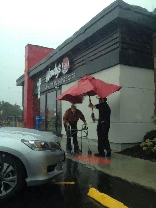 Empleado cubre de la lluvia a un anciano con una sombrilla de mesa