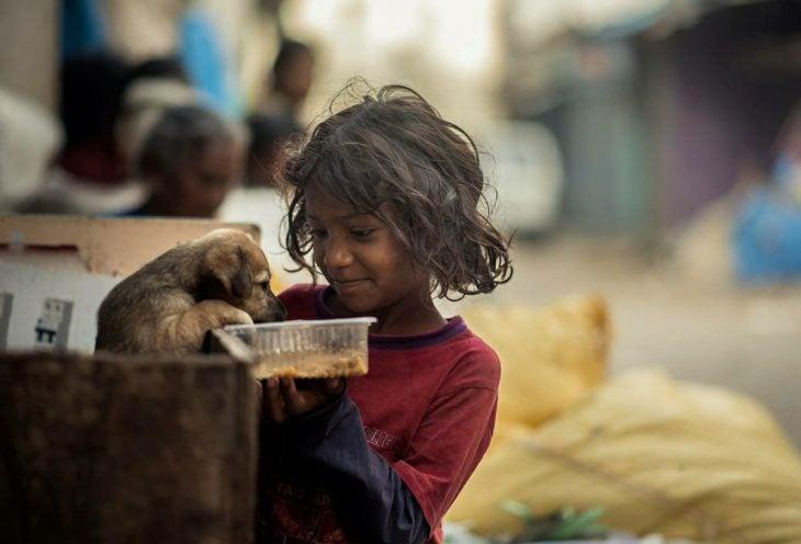 niña pobre alimentando a un perro