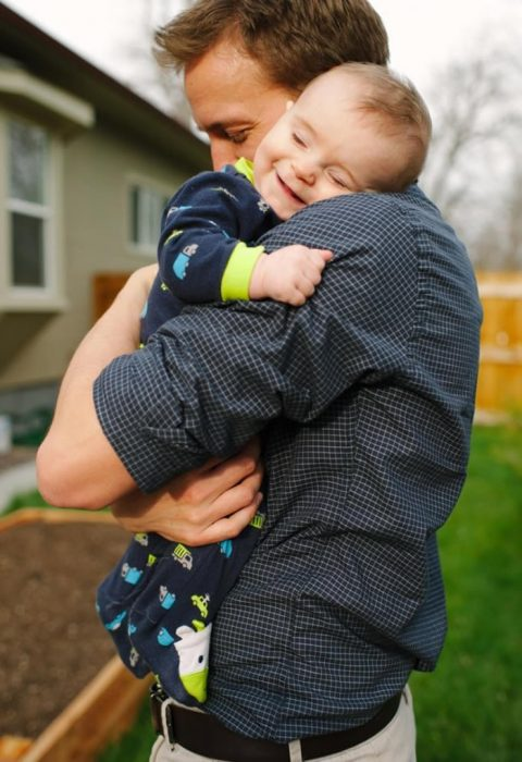 bebé sonriendo mientras abraza a su papá