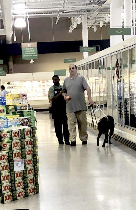 Un empleado ayuda a un invidente a hacer sus compras