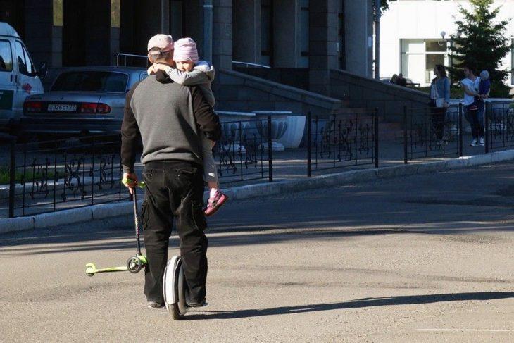señor en monociclo cargando a una niña