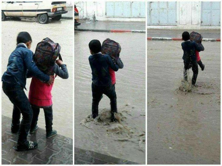 niño ayuda a hermana a cruzar calle inundada