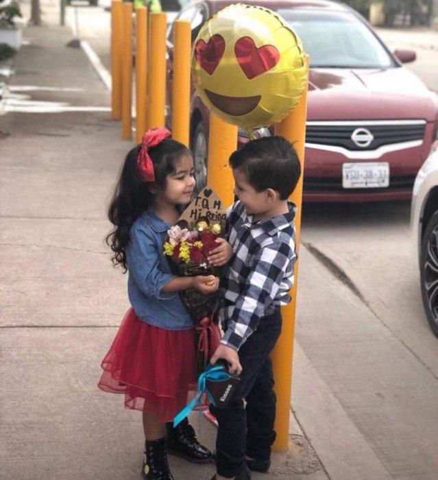 niño regala globo y flores a su novia