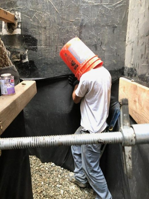 trabajador con balde en la cabeza