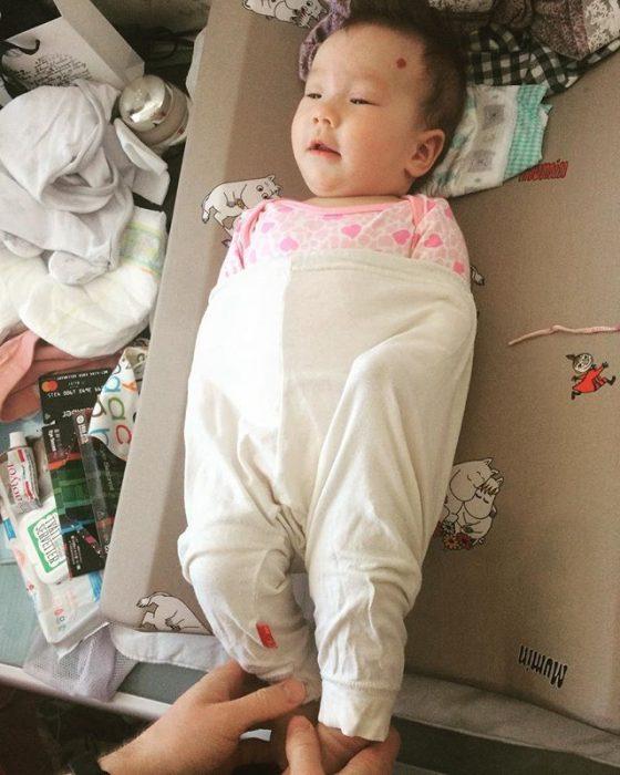 bebé con pantalón sobre los hombros