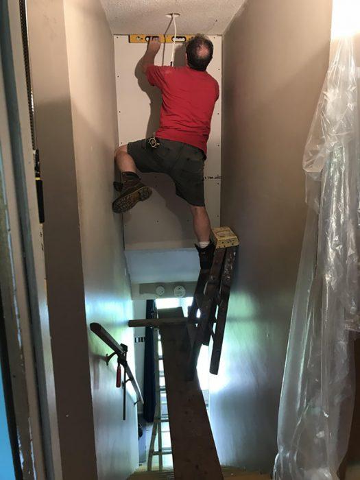 hombre sin protección pintando en el segundo piso de una casa