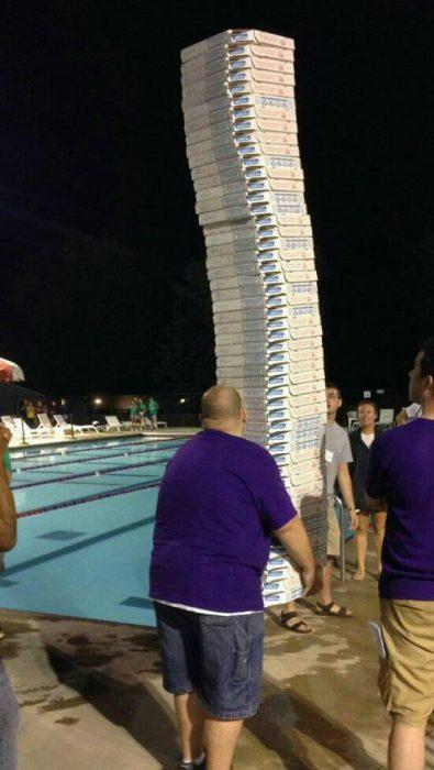 hombre cargando muchas pizzas