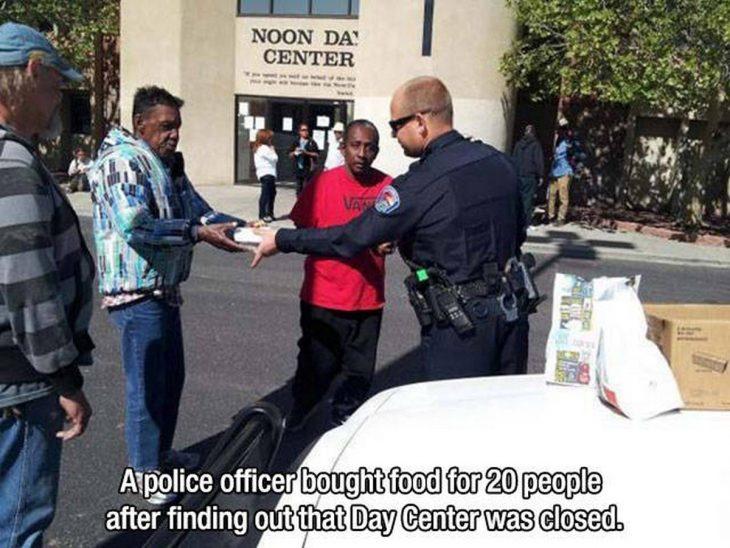 policía dando de comer a indigentes