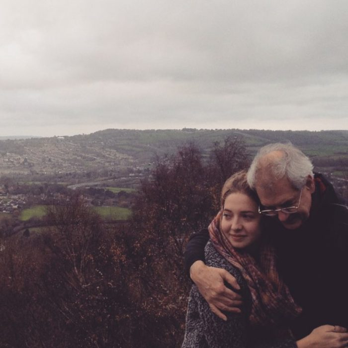 mujer abrazando a su padre con paisaje en el fondo