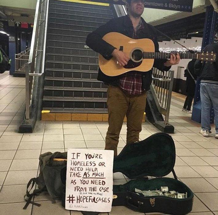 hombre toca la guitarra para recaudar dinero