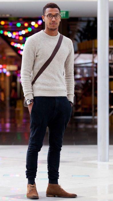 chico moreno con un suéter beige