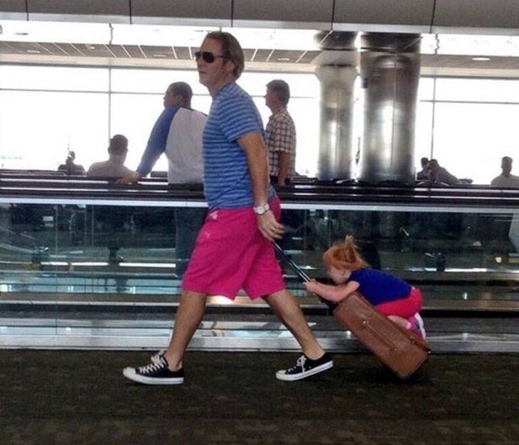hombre cargando una maleta que a su vez está cargando a una niña