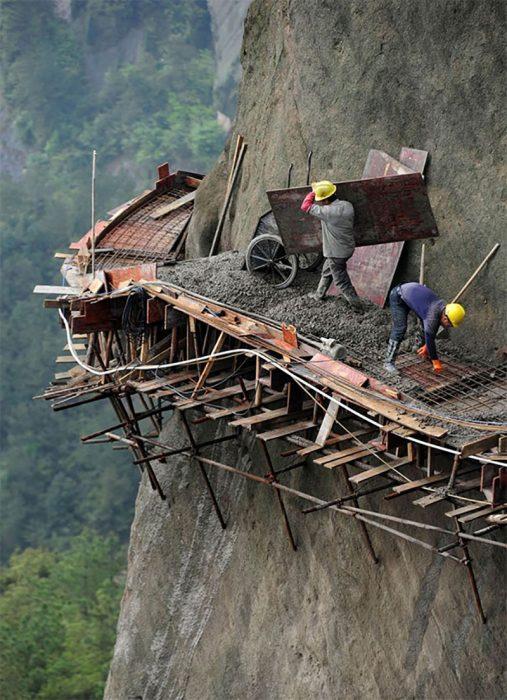 hombres construyendo camino muy pegadito a una colina